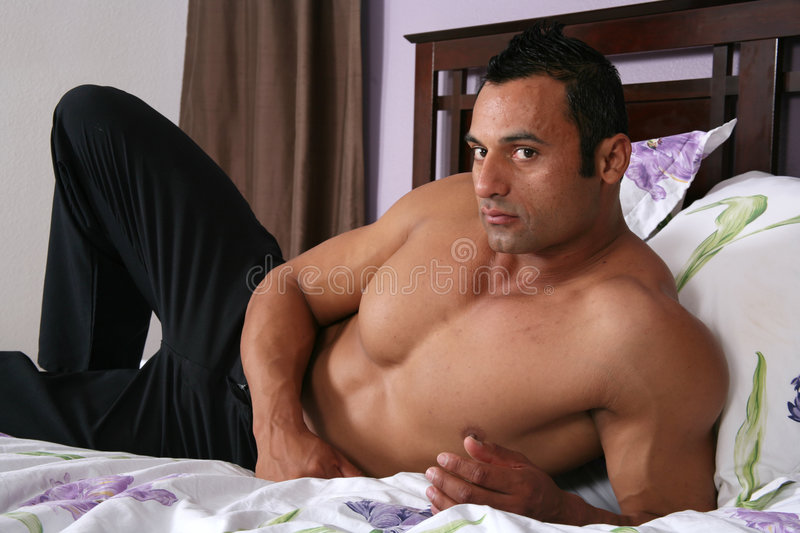 Male model. Lying on a bed in a bedroom royalty free stock images
