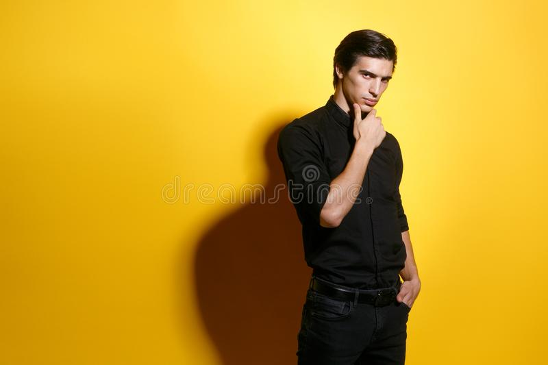 Portrait of a man in black, holding a hand in his pocket, looking at camera,  on yellow background, copy space. stock photos