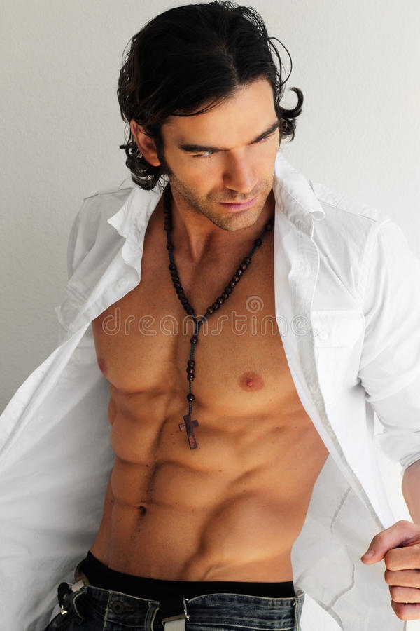 Man. Macho man opening shirt exposing muscular torso and abs against white neutral background stock image