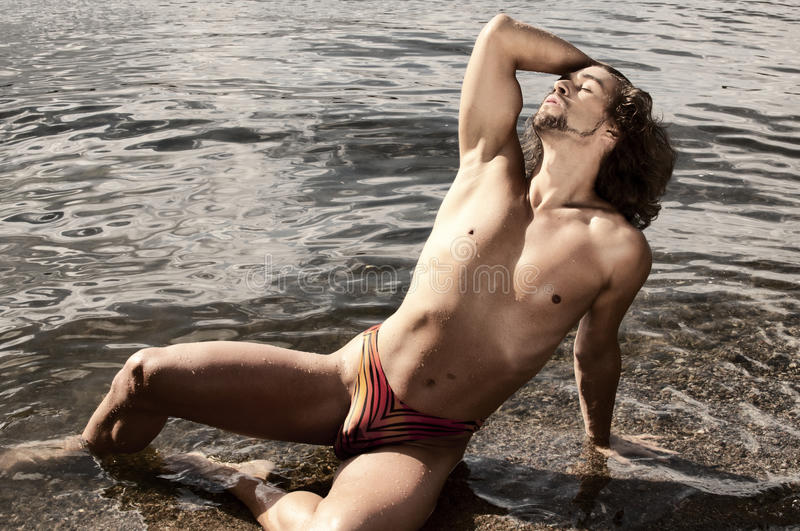 Man on a beach. Handsome young man in swim trunks stock photography
