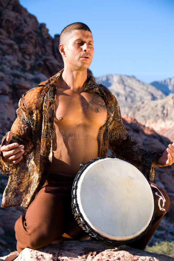 Man and drum. Muscular man with his shirt open about to play a drum. Taken outside stock images