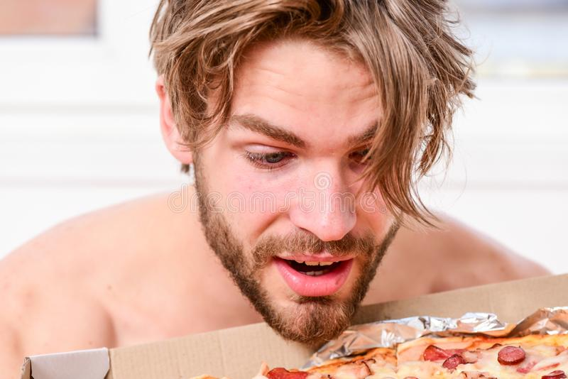man eat pizza lying on bed. Student is at home on the bed in a bright apartment eating a tasty pizza. Man bearded stock photography