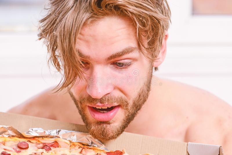 Sexy man eat pizza lying on bed. Student is at home on the bed in a bright apartment eating a tasty pizza. Man bearded royalty free stock photos
