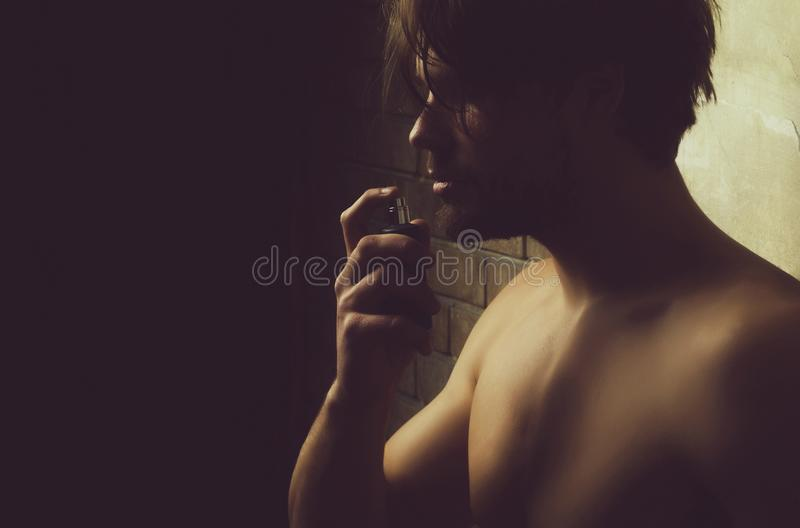 man with naked chest smelling perfume aroma stock photo