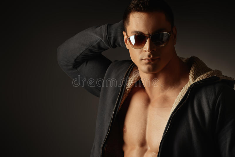 Man. Portrait of a muscular young man posing over dark background royalty free stock photography