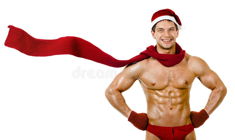 Man Santa Claus. The very muscular bronzed handsome Santa Claus in red muffler on white background, posture and smile, isolated stock image