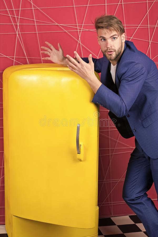 Sexy man in stylish jacket. confident businessman in suit. Businessman. unhappy man. Feel the success. Male formal. Fashion. Bright fridge household appliances royalty free stock photos