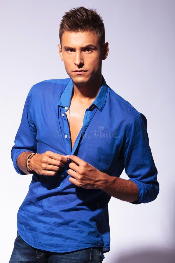 man unbuttoning blue shirt stock image