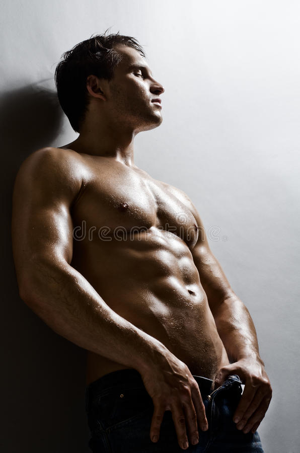 Man. The very muscular handsome guy on grey wall background royalty free stock photos
