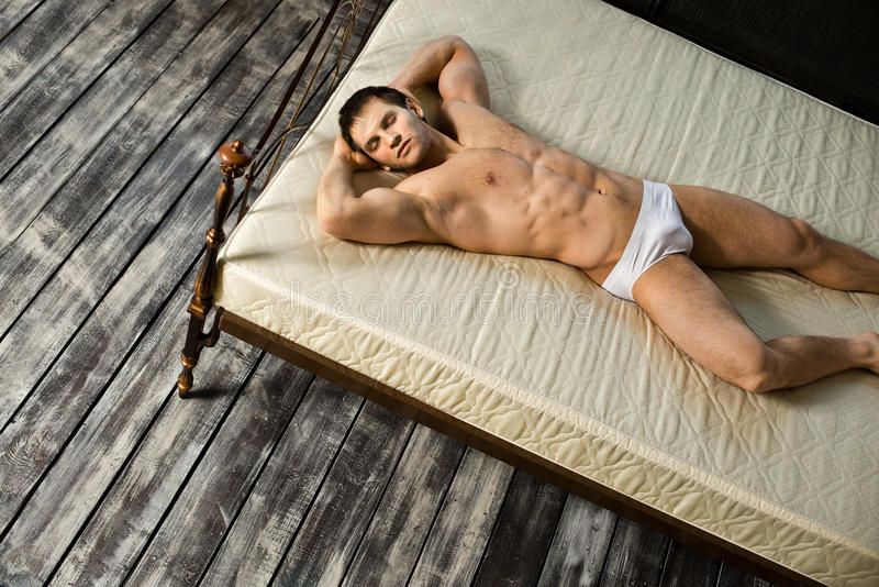 Man. The very muscular handsome guy, sleeping lie on bed, in bedroom royalty free stock photo