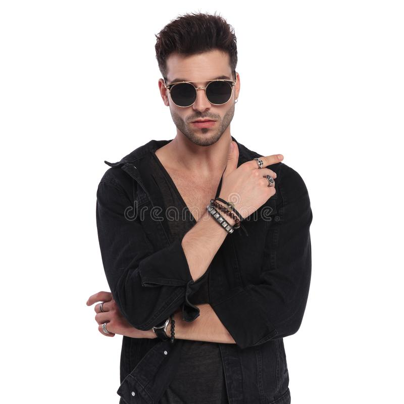 Man wearing black shirt shows his bracelets and rings. Portrait of man wearing a black shirt showing his bracelets and rings while standing on white background royalty free stock photography