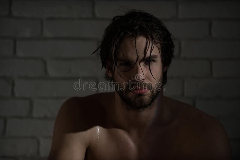 Sexy man with wet hair, muscular body in bath, shower stock photo