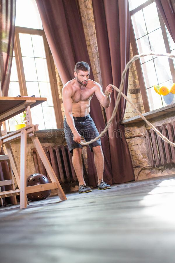 Man working out with ropes to train arm and shoulder muscles. Sort at home, concept, brutal male with naked torso training in living room stock images