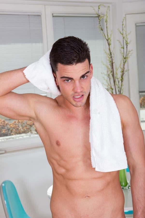 Sexy mannelijk die model met handdoek rond zijn hals wordt verpakt stock afbeelding