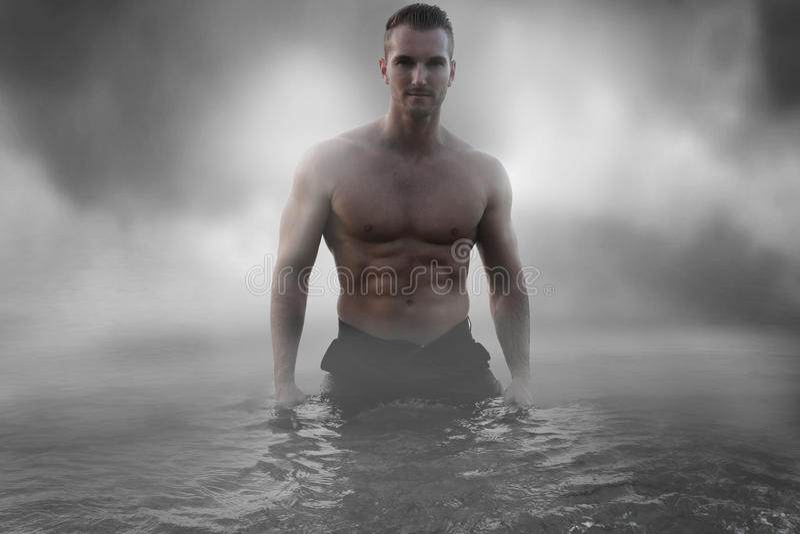 Sexy mannelijke status in het water royalty-vrije stock foto