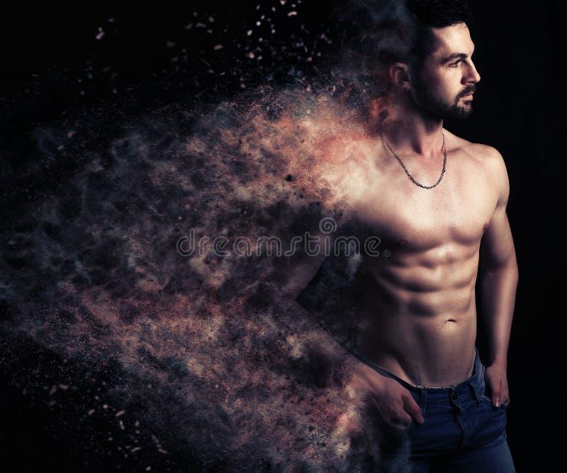 Sexy mannetje die een explosie van deeltjes creëren royalty-vrije stock fotografie