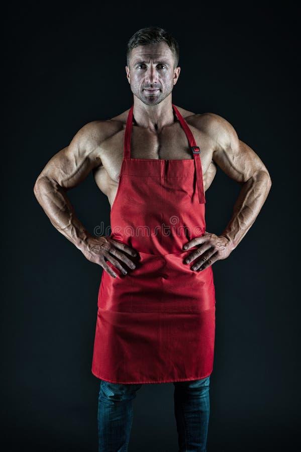 Sexy Mannkoch Mann mit dem muskul?sen Torso im Chefschutzblech cuisine M?nnliche Hausfrau Ehemann in der K?che grober Metzger Nah lizenzfreie stockfotos
