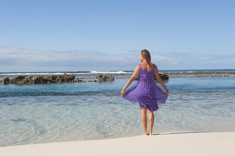 Mature Woman in Purple Dress. An attractive looking mature woman in her 50s, wearing a purple dress, is smiling happily and enjoying life at the beach, while royalty free stock photography