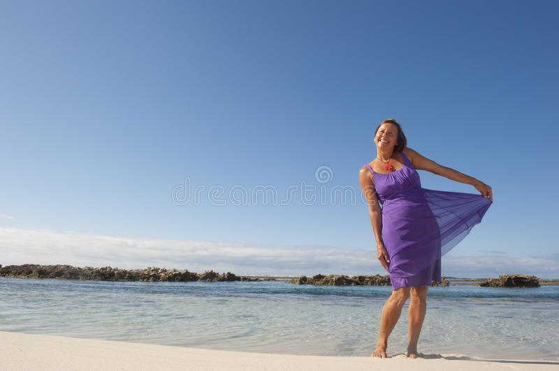 Mature Woman in Purple Dress. An attractive looking mature woman in her 50s, wearing a purple dress, is smiling happily and enjoying life at the beach, while stock image