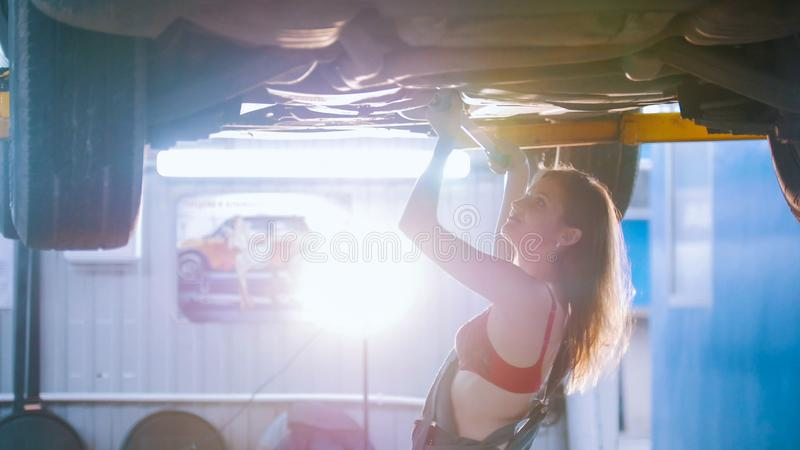 mechanic girl repairs the car with a spanner royalty free stock photography