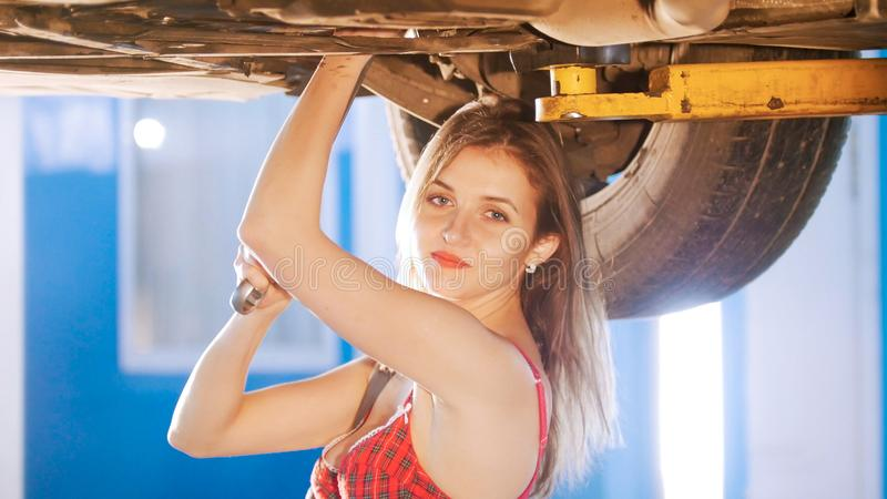 mechanic girl under the car with a spanner, looking in the camera royalty free stock images