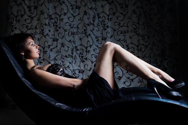 Sexy meisje in avondjurk die op de bank ligt stock afbeelding