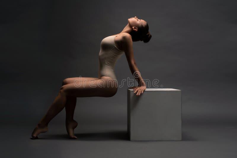 Sexy meisje in beige lichaam die haar overspannen achtermening stock afbeelding