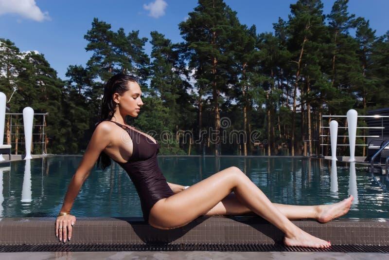 Sexy meisje die met perfect lichaam en lange benen dichtbij het zwembad in kuuroord zitten royalty-vrije stock fotografie