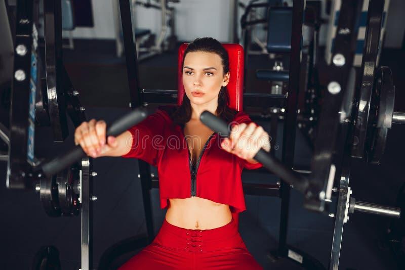 Sexy meisje die oefeningen in haar pectoral spieren in simulator doen stock afbeeldingen