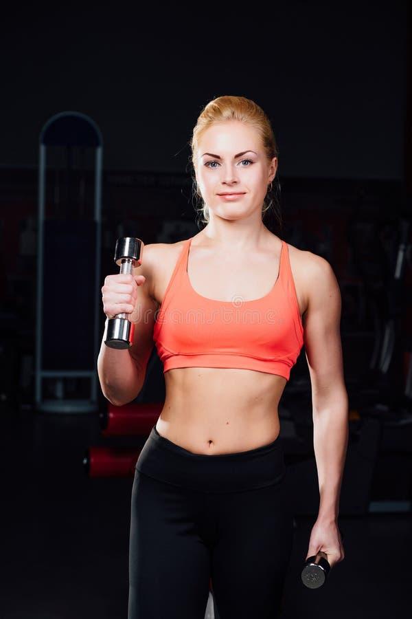 Sexy meisje die oefeningen in haar wapensbicepsen en triceps doen geschiktheid met domoren in de gymnastiek stock foto's
