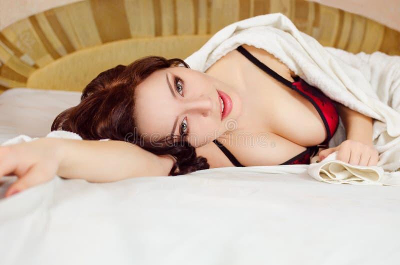 Sexy meisje die op bed liggen stock foto