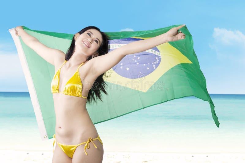 Sexy meisje met bikini en Braziliaanse vlag bij strand stock foto