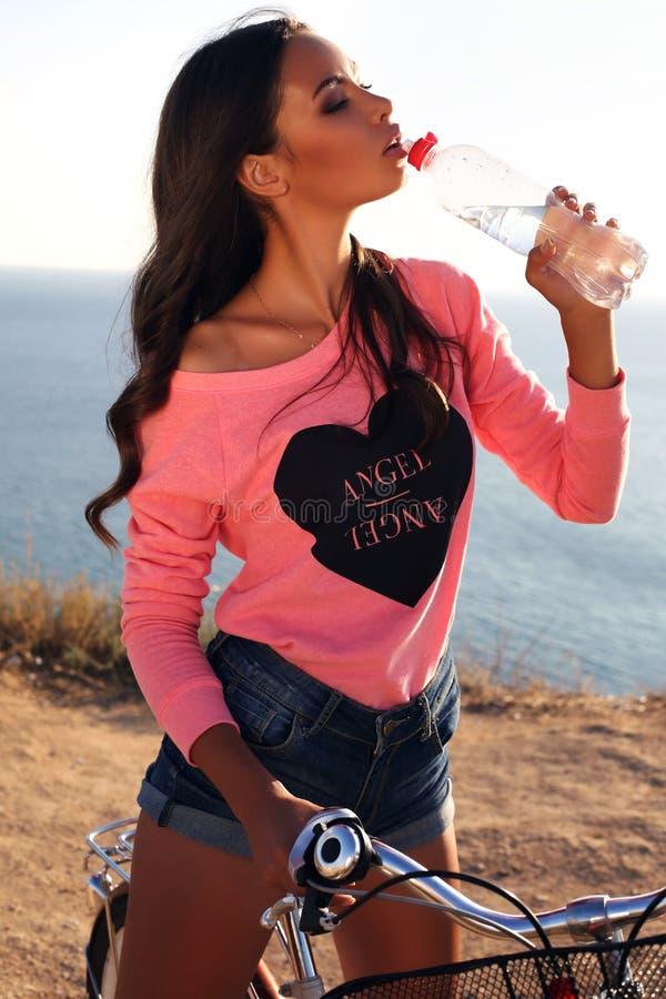 Sexy meisje met de donkere zitting van het haar drinkwater op fiets royalty-vrije stock afbeelding
