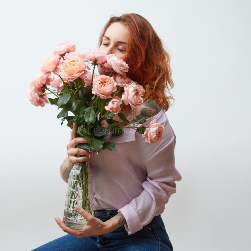 Sexy meisje met een boeket van gevoelige roze rozen in een transparante vaas op een grijze achtergrond met exemplaarruimte ST stock afbeeldingen