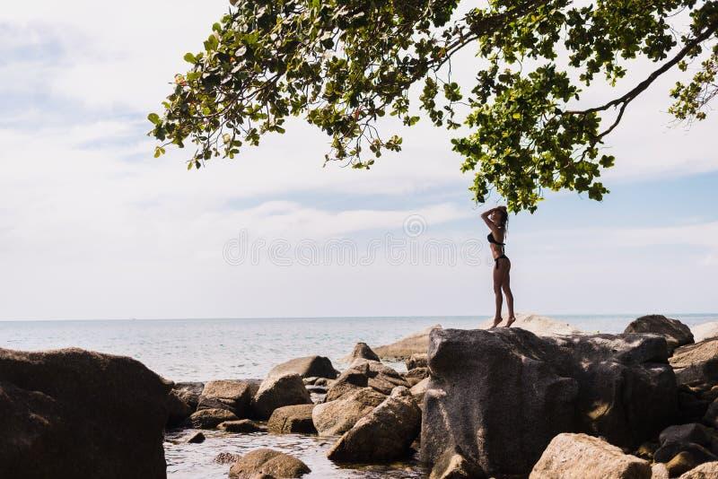 Sexy meisje met een sexy lichaam en een nat haar Charmante vrouw in een zwart zwempak dichtbij een rots op het strand Het model s stock afbeeldingen