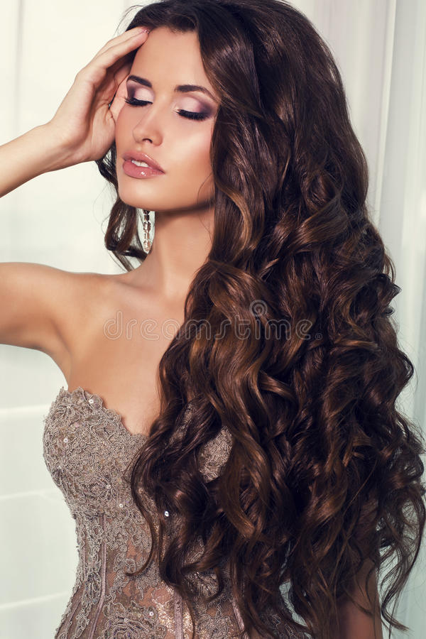 Sexy meisje met luxueus donker haar in elegante beige kleding stock afbeelding
