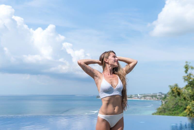 Sexy meisje Mooie vrouw het modelondergoed van de damebikini zit rand van water zwemt pool op het dak van het hotel van de luxeto royalty-vrije stock fotografie
