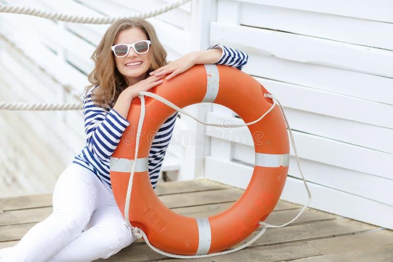 Sexy meisje tegen houten muur in de vorm van zeelieden met een reddingslijn en een GLB Het schieten in de studio op een wit royalty-vrije stock afbeelding