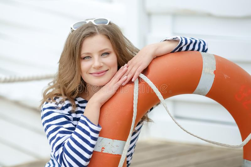 Sexy meisje tegen houten muur in de vorm van zeelieden met een reddingslijn en een GLB Het schieten in de studio op een wit royalty-vrije stock afbeeldingen