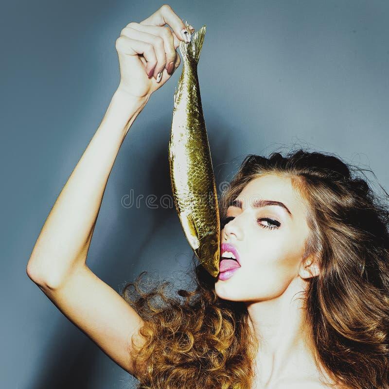Sexy meisje of vrouwenlik gouden haringen stock fotografie