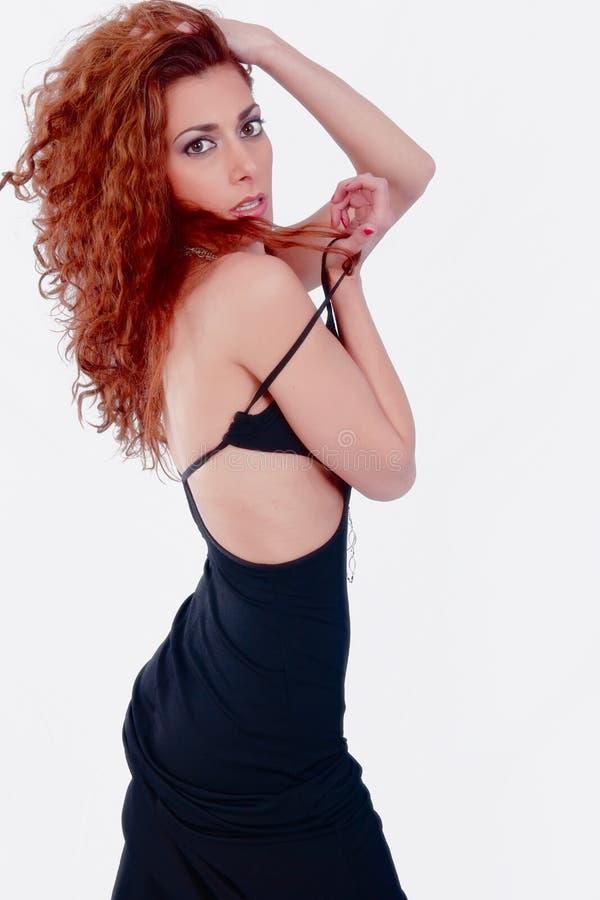 Sexy meisje in zwarte kleding met rood haar. stock foto