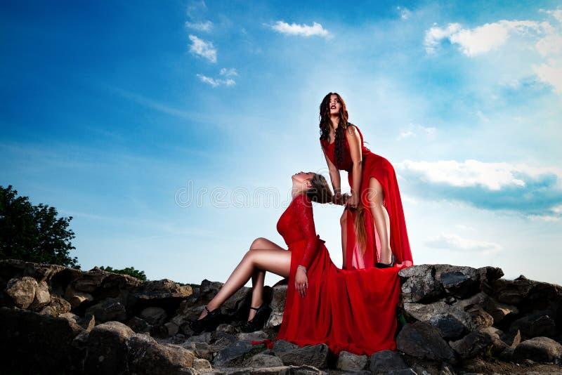 Sexy meisjes in het rode kleding stellen op oud rotskasteel met lange benen royalty-vrije stock foto's