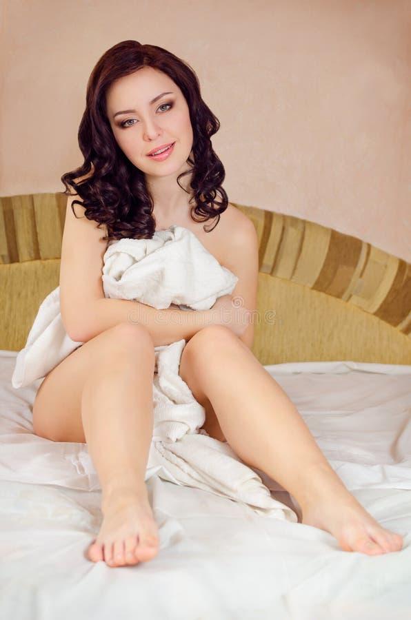 Sexy meisjeszitting op het bed royalty-vrije stock foto's