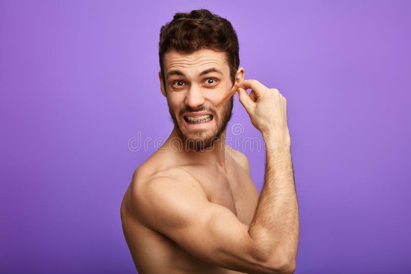 Sexy mens die pijnlijke ontharingsprocedure hebben stock afbeeldingen