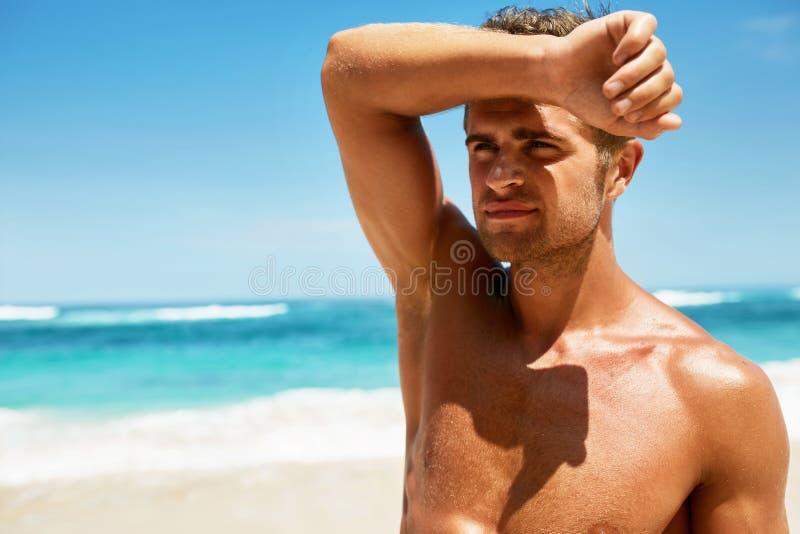 Sexy Mens op Strand in de Zomer Het mannelijke Ontspannen dichtbij Overzees royalty-vrije stock afbeeldingen