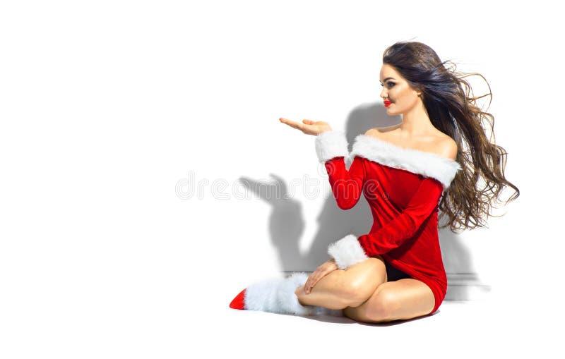 sexy mikołaja Bożenarodzeniowa piękno dziewczyna wskazuje rękę Brunetki młoda kobieta jest ubranym krótką czerwieni suknię fotografia stock