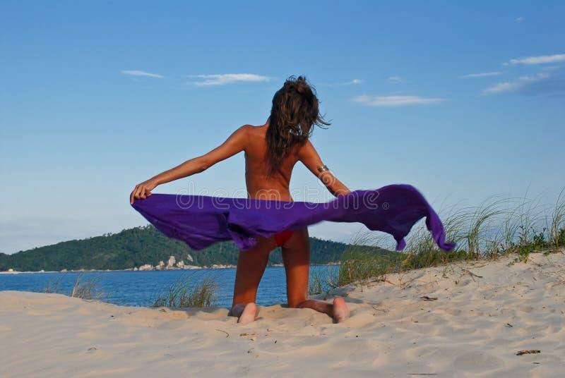 model on beach with purple sarong stock image