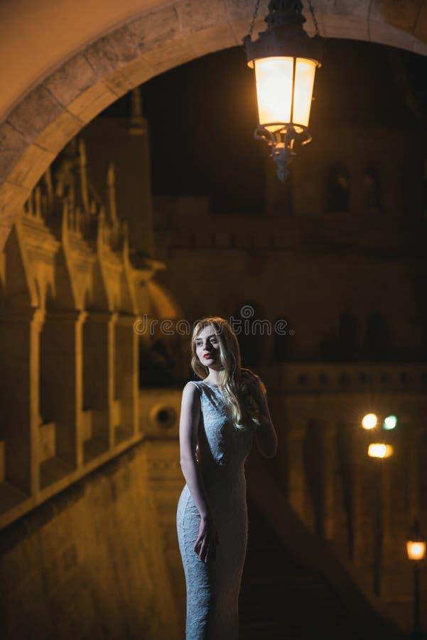 Sexy moderne schöne junge Frau im langen Abendkleid über Ansicht über Nachtstadt beleuchtet Hübsche Dame mit dem langen Haar stockbild