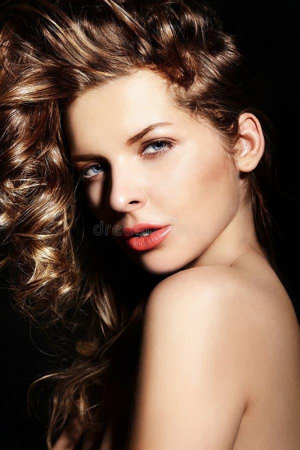Sexy modieus donkerbruin Kaukasisch jong vrouwenmodel met heldere make-up, met krullend healty haar met blauwe ogen grote lippen i stock foto