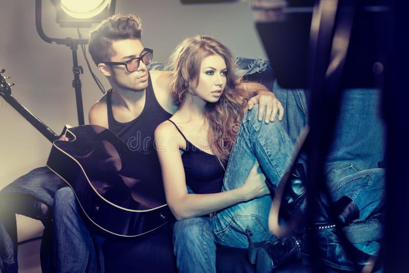 Sexy modieus paar die jeans dramatisch stellen dragen stock foto's